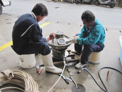 機械に付着したカルシウムの撤去作業